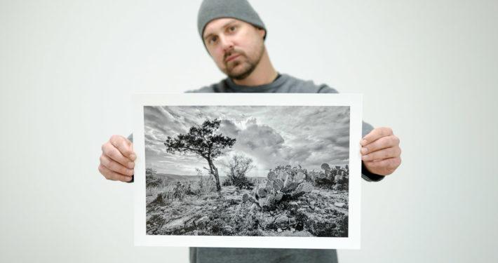 "Matt Mikulla holding ""Hill Country Delight"" black and white photograph"