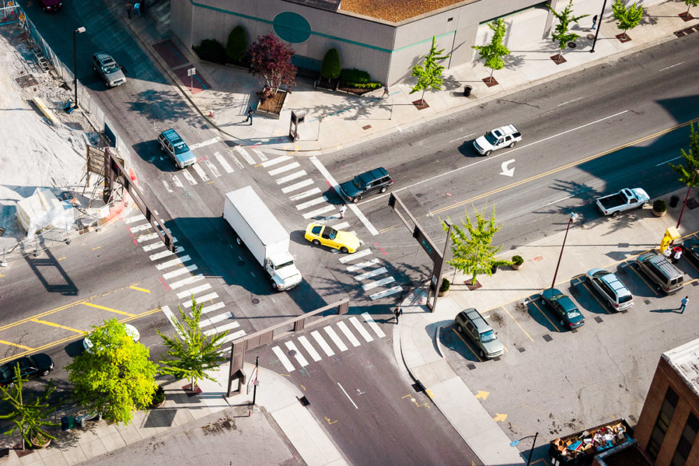 Photo of a traffic intersection with a white truck and yellow Corvette