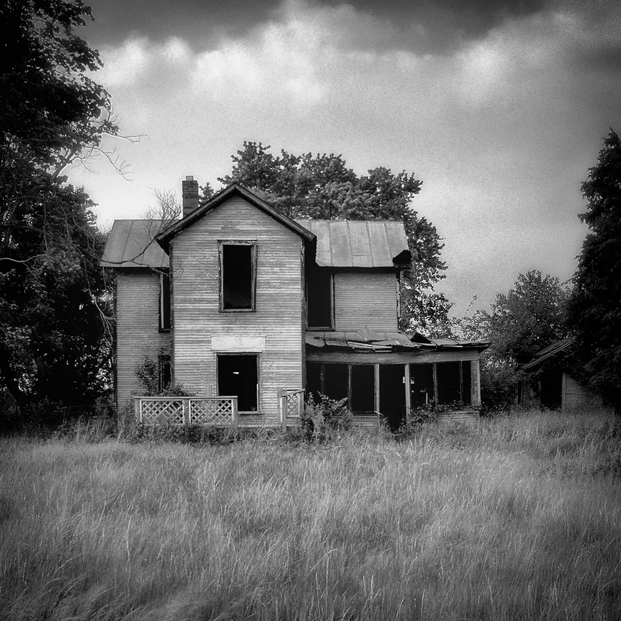 Empty fine art black and white photograph of an abandoned house