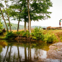 Swimming Hole - Color photograph of a woman standing near a swimming hole